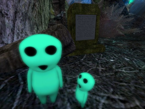 Image Description: Green, alien shaped creatures in front of a stone monument with English writing on it.