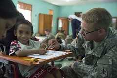 U.S. Army Spc. Norman Miller, assigned to the 84th Civil Affairs Battalion, visits with children from the Irmas Alma School for the Disabled. (U.S. Navy/MC2 Derek Stroop)