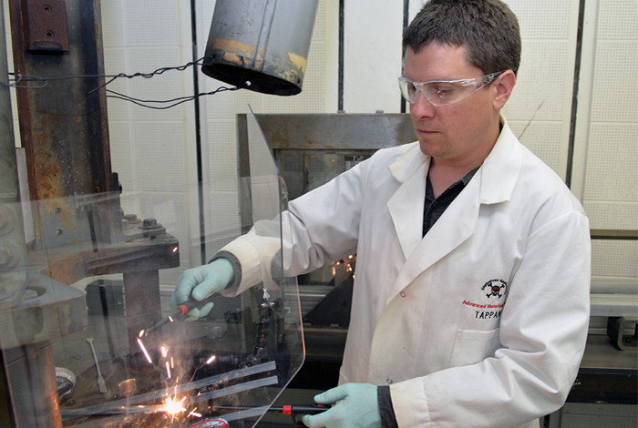 Los Alamos National Laboratory chemist Bryce Tappan ignites a small quantity of aluminum nanoparticle water mixture.  In open air, the compound burns like a Fourth of July sparkler.