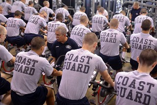 James Schena, a physical fitness instructor at U.S. Coast Guard Training Center Cape May, instructs recruits in the proper way to ride a stationary bike, Sept. 10, 2014. The training center recently purchased 95 Lifecycle GX indoor bikes, which are more compatible with interval training and will reduce the amount of maintenance required to keep them operational. (U.S. Coast Guard photo by Chief Warrant Officer John Edwards)