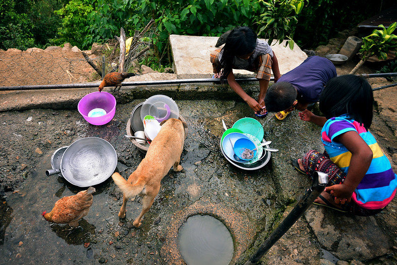 Village children wash dishes at communal washing areas placed in between houses. Households do not have individual water systems.