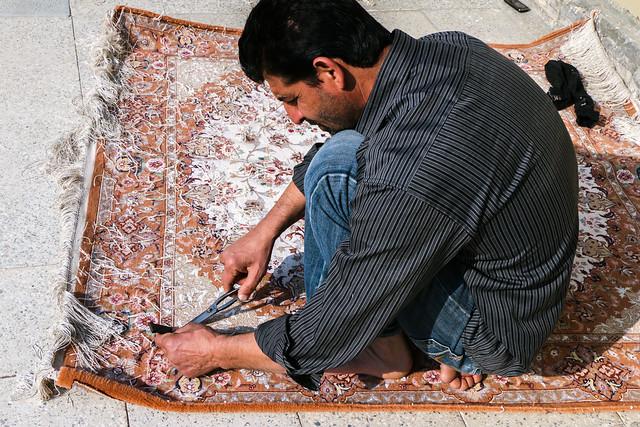 Finishing a carpet, Isfahan grand bazaar イスファハン、バザールの工房で絨毯の仕上げをする男性