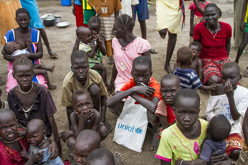 A group of refugees listen to information on sanitation and hygiene