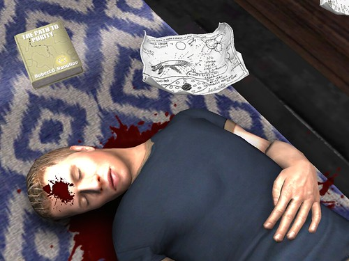Image Description: A close up of a man lying on the floor, shot in the forehead. A book and several crumpled papers are near him.