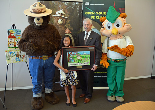 Audrey Morga, national winner of the 2015 National Smokey Bear and Woodsy Owl poster, standing with U.S. Forest Service Chief Tom Tidwell, Smokey Bear and Woodsy Owl