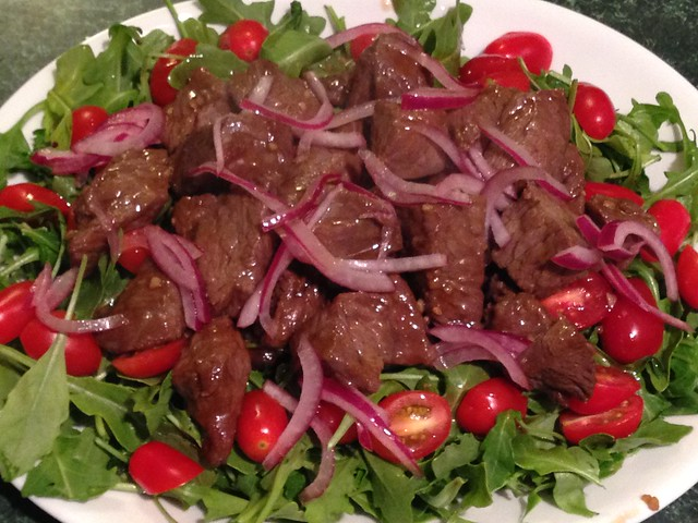 Vietnamese Shaking Beef Bo Luc Lac with watercress, tomatoes, and pickled onions
