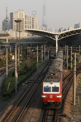 Electric locomotive SS7E 0087 departs Shanghai Railway Station with a sleeper train