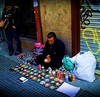 Making artful objects from refreshment tin cans. Street artist in Madrid