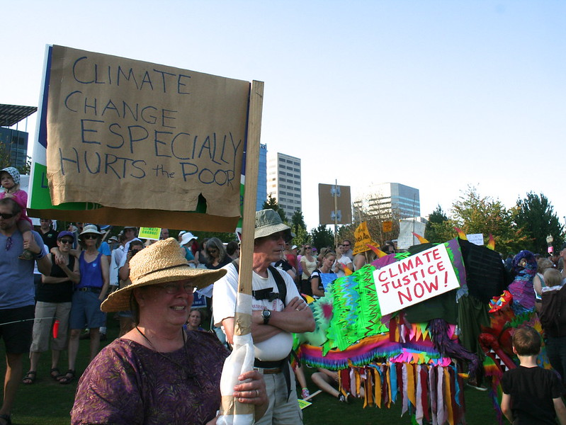"a woman holds a sign reading ""climate change especially hurts the poor"""