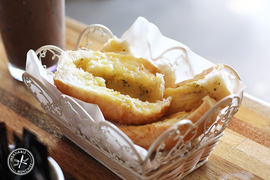 Garlic bread is topped with melted cheese and served in a pretty white basket.