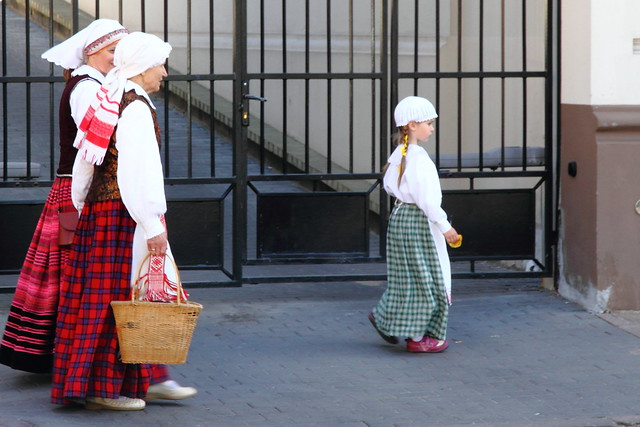 Two  women and a girl in traditional clothing of Lithuania in old town of Vilnius.