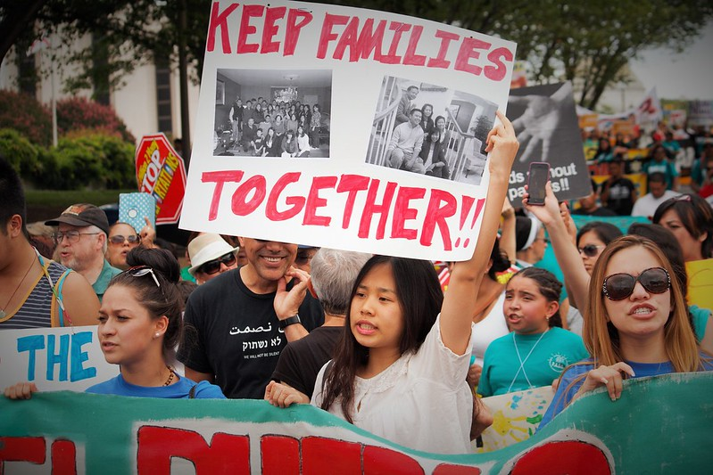 "a protester holds a sign that says ""keep families together"""