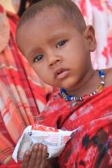 Madina, 18-months-old, holds onto her Ready-to-Use Therapeutic Food (RTUF) supplement at the Dubti health centre.
