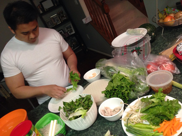 Husband preparing fresh shrimp rolls with vegetables