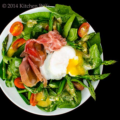 Asparagus and Spinach Salad topped with prosciutto and a poached egg, overhead view on black