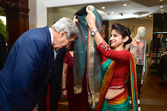 U.S. Secretary of State John Kerry bows to receive a scarf during a traditional arrival ceremony at his hotel in New Delhi, India, on July 30, 2014, after he traveled for a Strategic Dialogue with Commerce Secretary Penny Pritzer. [State Department photo/ Public Domain]