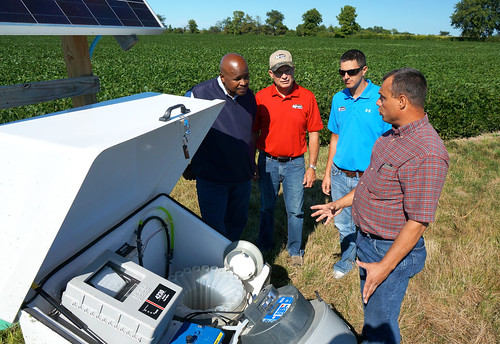 U.S. Department of Agriculture (USDA) Agricultural Research Service (ARS) engineer Kevin King (right) explains an edge of field water quality monitoring station to Ohio State Conservationist Terry Cosby, farm owners Joe and Clint Nester in the Western Lake Erie Basin near Bryan, Ohio on Thursday, Aug. 14, 2014. The device allows tracking of both surface and underground water moving thru field tile. Monitoring stations results help determine what may be best farming practices on different types of soil in the watershed. USDA photo by Garth Clark.