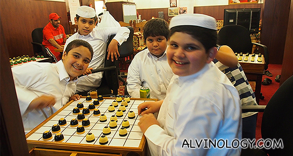 Qatari kids playing some sort of chess game with pieces that look like puddings to me