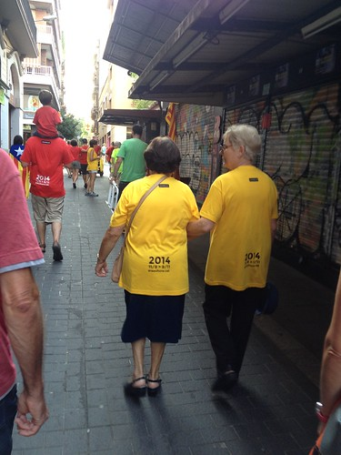 Two older yellow t-shirted demonstrators in Gràcia after the demonstration