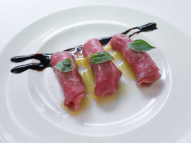 Beef carpaccio with cheese, basil, olive oil and balsamic vinegar