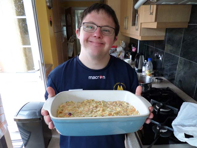 Chris holding up his Courgette bake and smiling