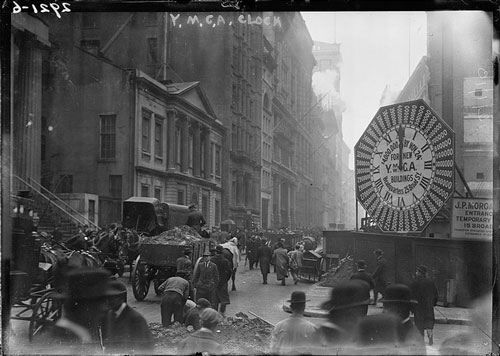 Wagons trundle along Manhattan streets past a YMCA clock sing (circa late 19th century)