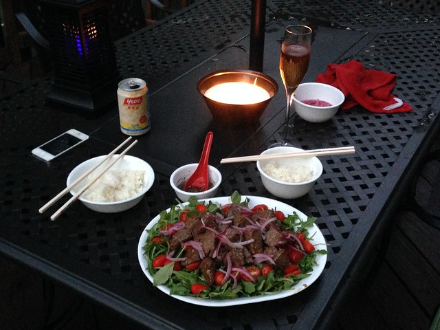 Dinner table set with Shaking Beef, bowls of rice, and lime dipping sauce.