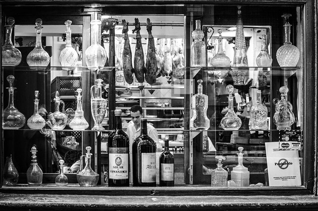 Decorative bottles line a restaurant window in Granada, Spain.