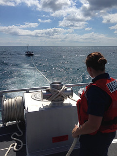 A crew member from Coast Guard Station Sheboygan, Wis., aboard a 45-response boat, stands tow-watch while towing an 18-foot pleasure craft on Lake Michigan July 8, 2014.   The response boat crew and a good Samaritan assisted two men aboard the vessel after it began taking on water about 3 miles east of Port Washington, Wis.   U.S. Coast Guard photo courtesy of Coast Guard Station Sheboygan