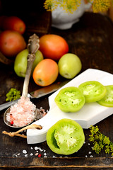 Different varieties of tomatoes on wooden backgrou…
