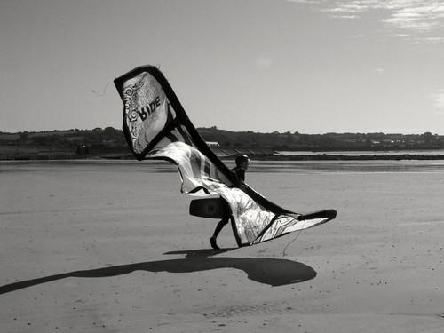 Kite Surfer preparing for flight at Gazon, Guernsey.