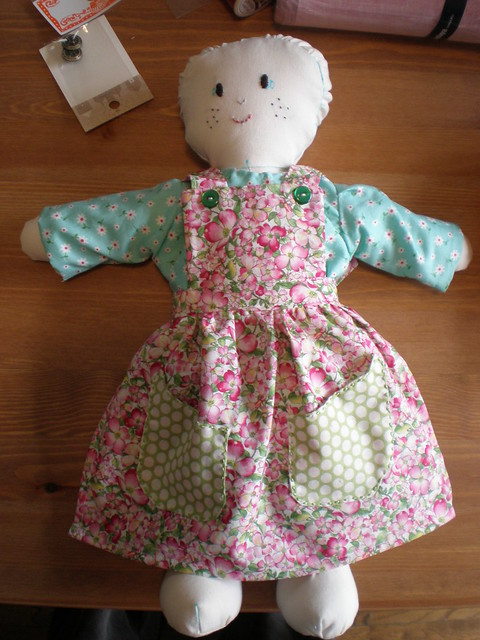 Doll in dress and pinnafore