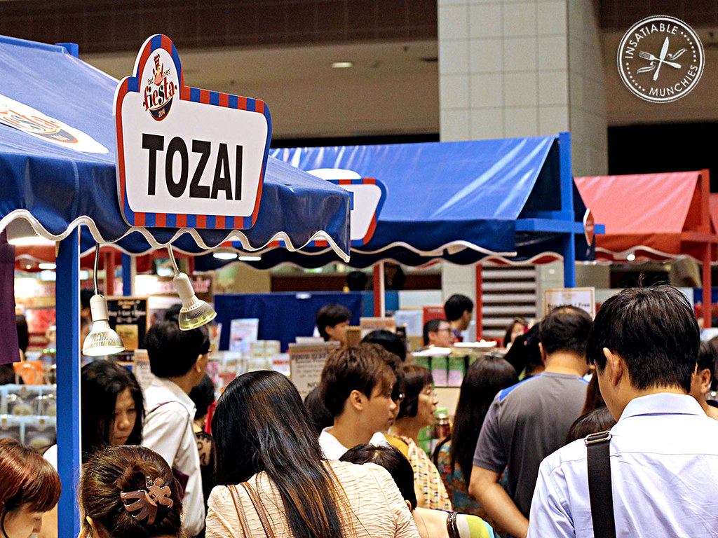 Singaporeans crowd around the stalls exhibiting their wares at the annual Takashimaya Food Fair