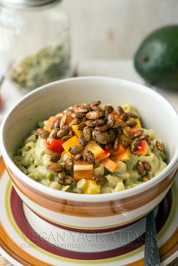 A striped bowl with Avocado Mac with Pepita Bacon inside, on a matching plate