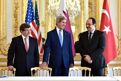 U.S. Secretary of State John Kerry stands with Turkish Foreign Minister Ahmet Davutoglu and Qatari Foreign Minister Khalid Al Attiyah at the U.S. Ambassador's Residence in Paris, France, on July 26, 2014, before a trilateral meeting focused on reaching a cease-fire in the fighting between Israel and Hamas in the Gaza Strip. [State Department photo/ Public Domain]