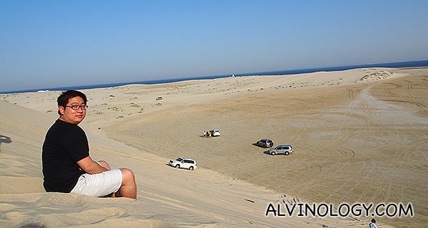 Me seated at the top of a steep sand dune slope