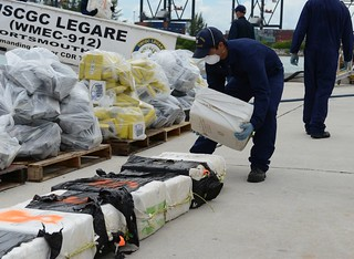 A crew member aboard the Coast Guard Cutter Legare stacks a bale of cocaine during a contraband offload at Coast Guard Base Miami Beach, Fla., Sept. 4, 2014. The offload is the result of two successful drug interdictions in the Caribbean Sea. (U.S. Coast Guard photo by Petty Officer 3rd Class Mark Barney)