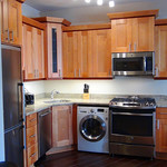 Tall view of kitchen with granite counters and quality appliances including washer dryer and dishwasher