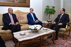 U.S. Secretary of State John Kerry and Egyptian Foreign Minister Sameh Shoukry sit side-by-side as they meet with Egyptian President Abdel Fattah al-Sisi at the Presidential Palace in Cairo, Egypt, on July 22, 2014, to discuss a possible ceasefire between Israeli and Hamas forces fighting in the Gaza Strip. [State Department photo/ Public Domain]