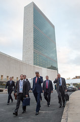 U.S. Secretary of State John Kerry talks on his cellphone as he departs the United Nations Headquarters in New York following a Security Council discussion about Iraq on September 19, 2014. [State Department photo/ Public Domain]