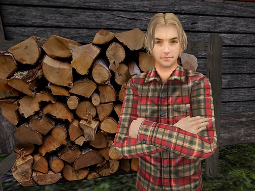 Image Description: A man standing in front of a wood pile.