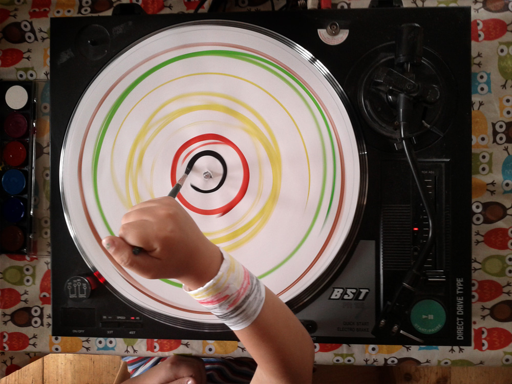 Kind malt mit dem Plattenspieler und Wasserfarben Kreise