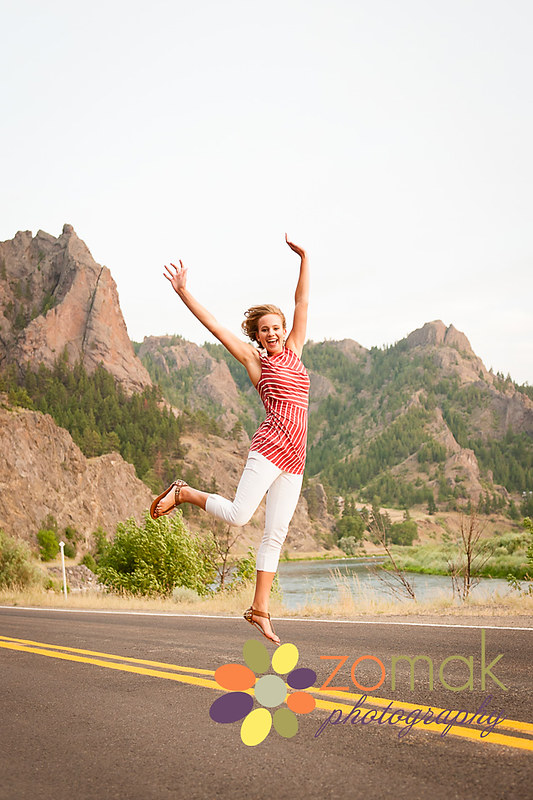 Class of 2015 senior jumps for joy with mountains and Missouri river in the backdrop.