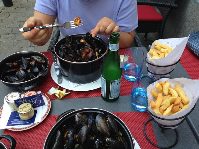 A table with mussels and french fries and bottled water