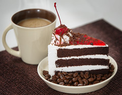 chocolate cake on a white plate and coffee