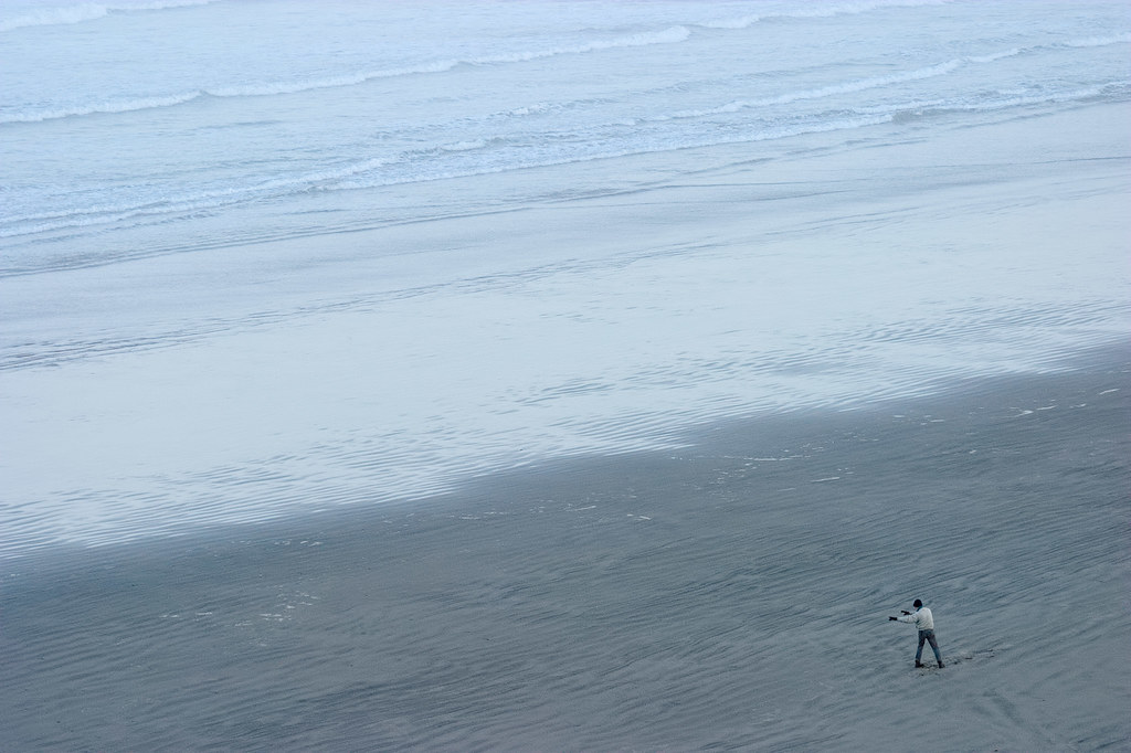 A man exercises at dawn on Nye Beach in Newport, Oregon