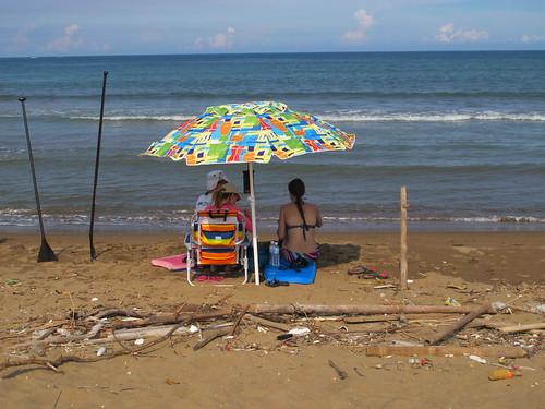 幾位外國遊客在沙灘上插著洋傘休息聊天,身旁卻布滿了浪潮帶來的垃圾。攝影:郭政佑。