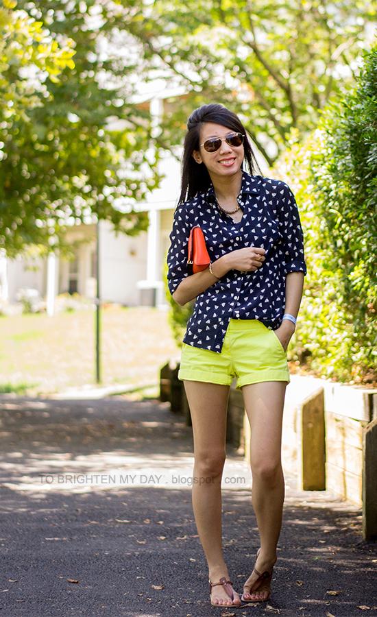 printed silk blouse, yellow shorts, orange clutch