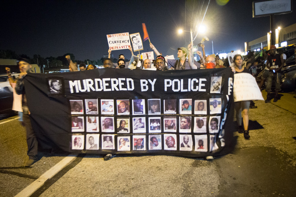 "protesters holding a sign that says ""murdered by police"" and has the faces of a dozen black men"