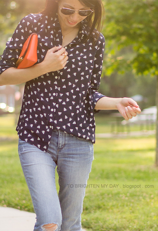patterned silk top, orange clutch, distressed jeans